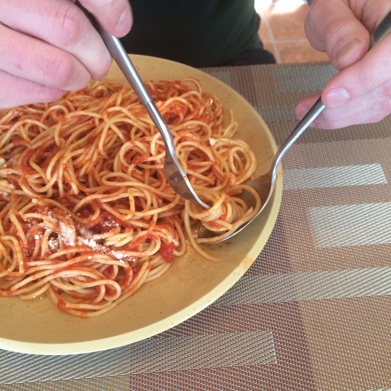 Using a spoon to put spaghetti on a fork